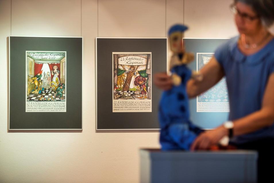 Evelies Baumann, die Leiterin des Coswiger Stadtmuseums Karrasburg, richtet die von Gottfried Reinhardt geschaffene Kasperpuppe. An der Wand sind Plakate der Radebeuler Kasperiade zu sehen, die Bärbel Kuntsche gestaltet hat. Sie hat das Bild des Puppenth
