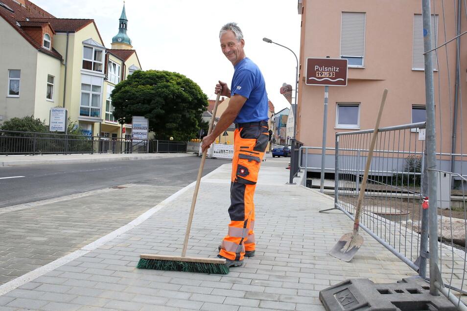 Noch einmal alles saubermachen, damit der Verkehr bald über die neue Brücke in Pulsnitz rollen kann. Jens Schwarzbach von der Baufirma freut sich, dass der Bau endlich fertig ist.