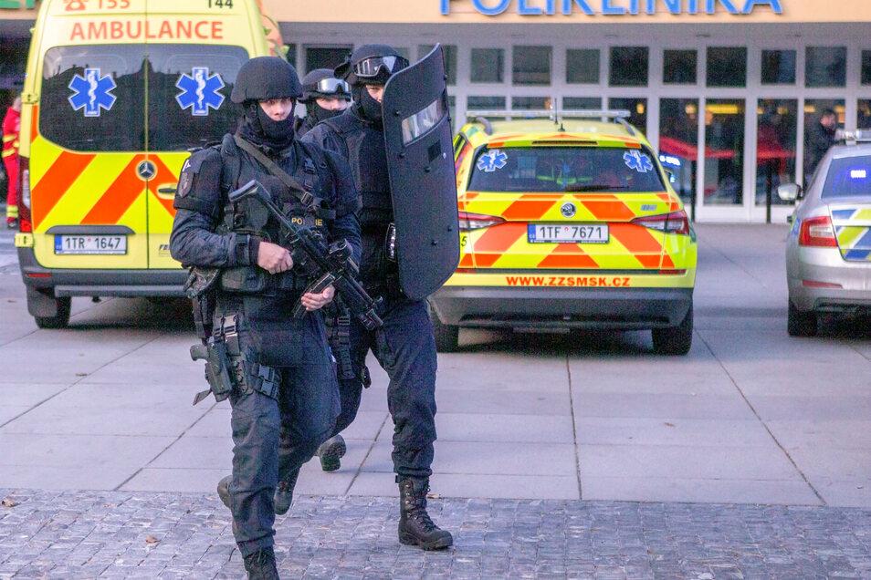 Drei Polizisten gehen über den Parkplatz des Universitätsklinikums.