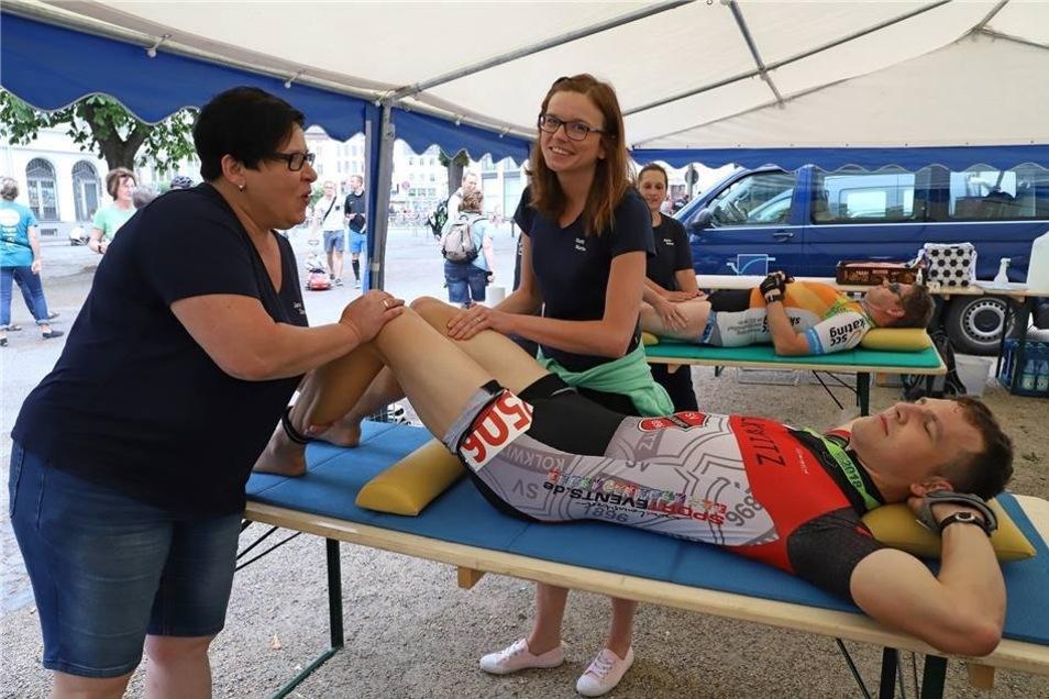 So ein langer Lauf ist schon eine Belastung. Der Läufer rlässt sich die Beine von zwei Physiotherapeutinnen durchkneten.