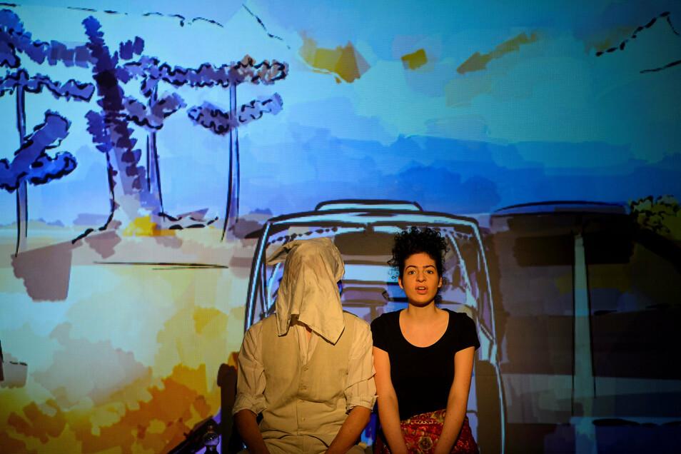 """Hannah Götze spielt das äthiopische Mädchen Fana in """"Endland"""" im Zittauer Theater vor Kulisse mit Bildern von Modi Jeroushi."""