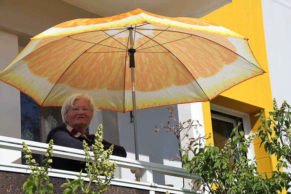 Die 78-jährige Edeltraud Tentschert genießt den Ausblick von ihrem Balkon und freut sich über die frisch gemalerte Fassade. Sie hat extra einen farblich dazu passenden neuen Sonnenschirm gekauft.
