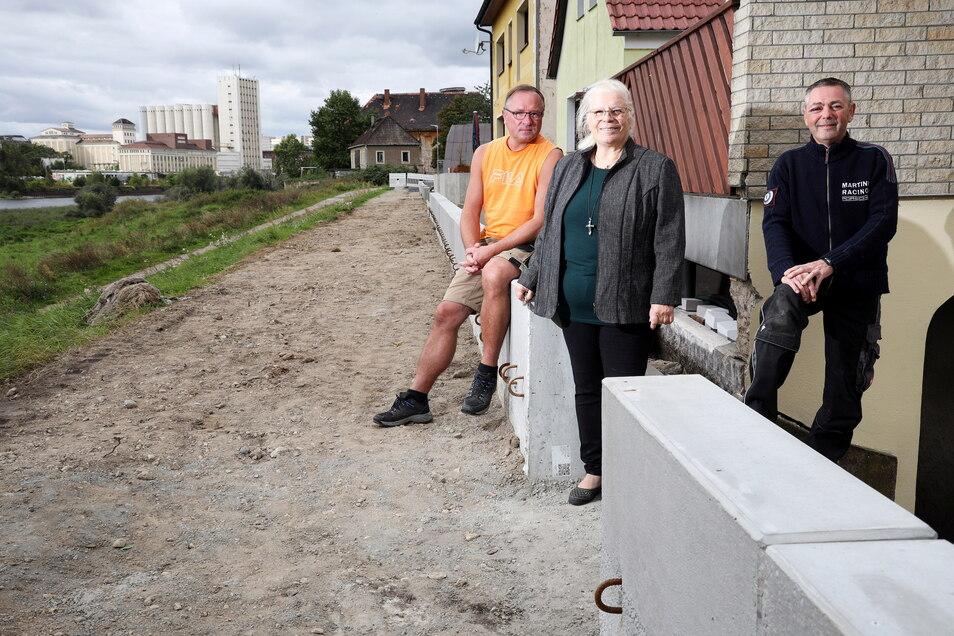 Waldemar Kowolik (l.), Charlotte Diehm und Daniel Kühne aus Promnitz an der neu errichteten Mauer vor ihren Grundstücken. Sie sind vor allem froh, dass an ihrer Straße nun etwas passiert.