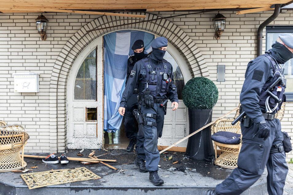 Polizisten verlassen ein Haus. Bei Ermittlungen gegen Kriminelle waren in drei Bundesländern mehr als 1.400 Beamte im Einsatz.
