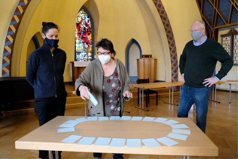 Pfarrerin Annegret Fischer (l.) und Rechtsanwalt Oliver von Gregory beobachten wie Uta Fink im Luthersaal der Friedenskirche den Gewinner des Kirchspiel-Rätsels zieht.
