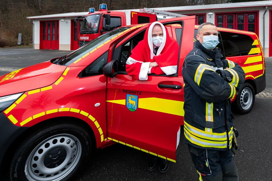Der Weihnachtsmann und Ortswehrleiter Lars Fernbach: neuer Wagen für die Mannschaft, dahinter das Fahrzeug für den Katastrophenschutz..