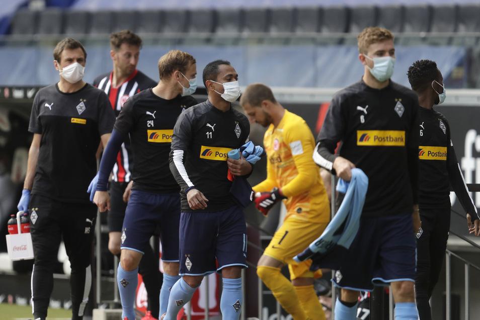 Während Frankfurts Torwart Kevin Trapp (in Gelb) bereit ist fürs Spiel, gehen die Ersatzspieler von Borussia Mönchengladbach zur Bank - sie tragen den vorgeschriebenen Mund-Nasenschutz: ein Merkmal des Neustarts in der Fußball-Bundesliga.