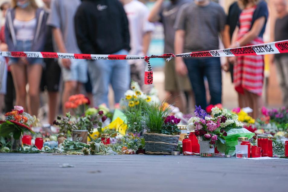 Trauerkerzen und Blumen liegen vor einem Kaufhaus in der Innenstadt, in dem ein Mann Menschen mit einem Messer attackiert hatte.