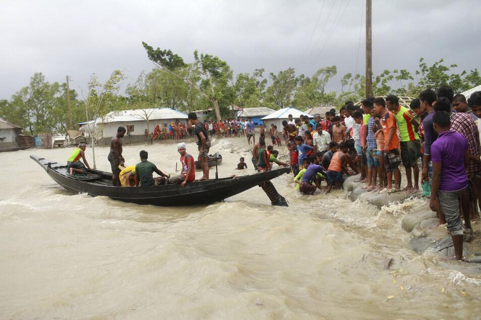 Ein Boot bringt in Shyamnagar (Bangladesch) vor der Ankunft des Zyklons «Amphan» Menschen ans Land, während Einheimische einen Damm überprüfen.
