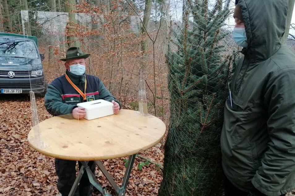 Revierförster Jens Lippmann kassiert im Wald hinter einer Plexiglasscheibe. Die 15-Kilometer-Regel reduzierte jedoch den Umsatz beim Weihnachtsbaum-Verkauf.