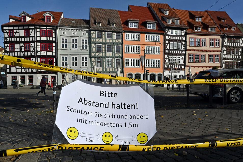 """""""Bitte Abstand halten!"""" steht auf einem Schild am Domplatz inmitten der Erfurter Altstadt."""