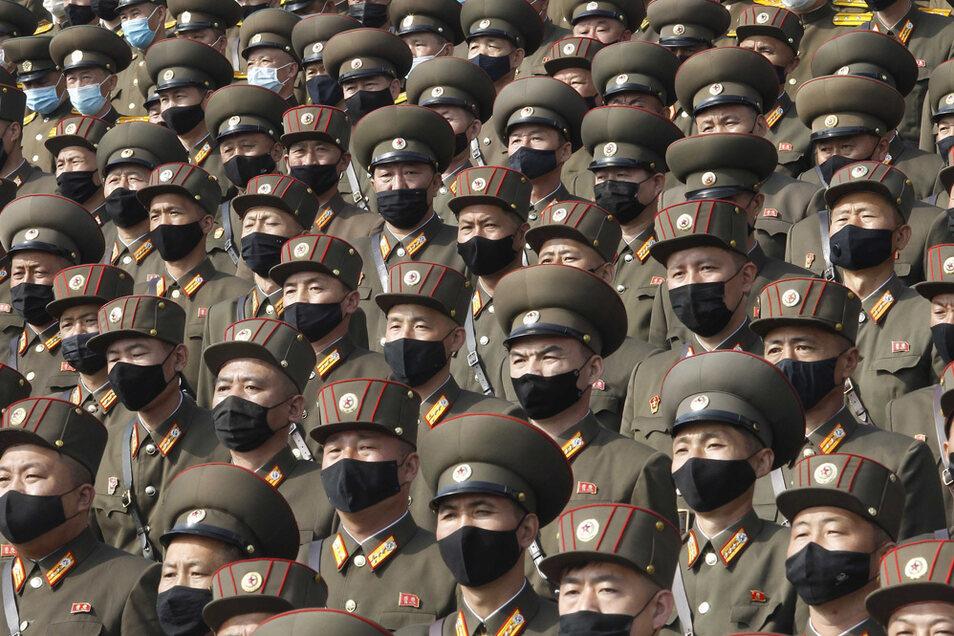 Soldaten mit Mund-Nasen-Schutz und Uniform stehen zur Begrüßung des 8. Kongresses der Arbeiterpartei Koreas auf dem Kim-Il-Sung-Platz.