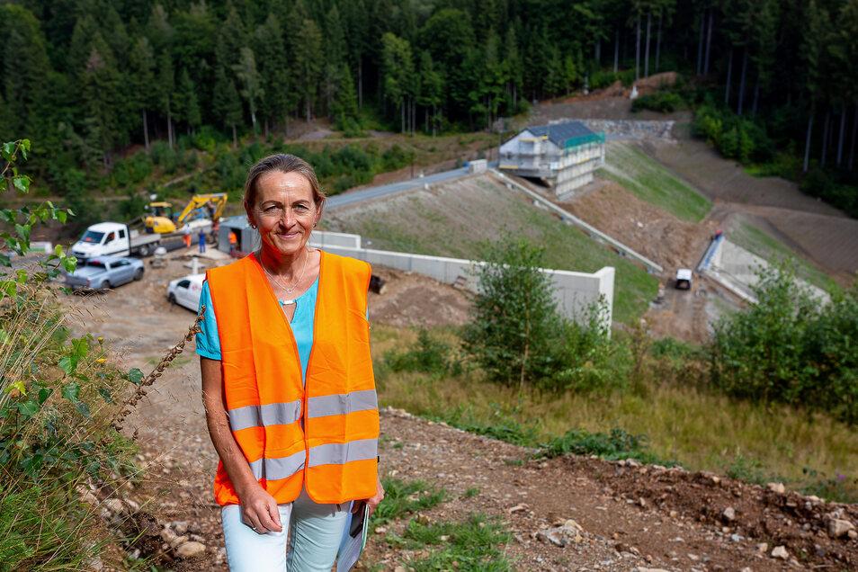 Betriebsleiterin Birgit Lange steht vor dem fertigen Hochwasserschutzdamm im Pöbeltal. Noch laufen die Feinarbeiten, die sich auf das Betriebsgebäude im Hintergrund konzentrieren.  Fotos: Karl-Ludwig Oberthür