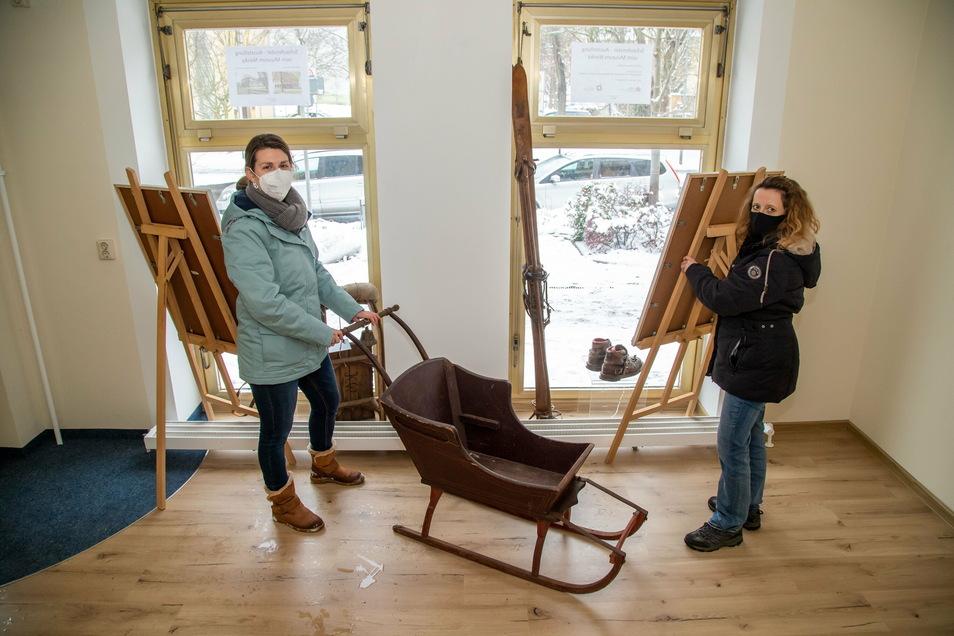 Die Museumsmitarbeiterinnen Claudia Wieltsch und Heike Mücke dekorieren leere Schaufenster mit Elementen aus ehemaligenSonderausstellungen im Raschkehaus und Wachsmannhaus.