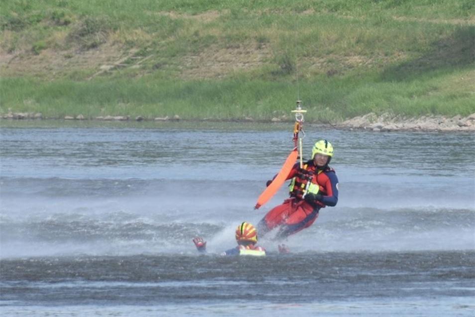 Mit der orangefarbenen Schlaufe sichert der Helfer die im Wasser treibende Person.