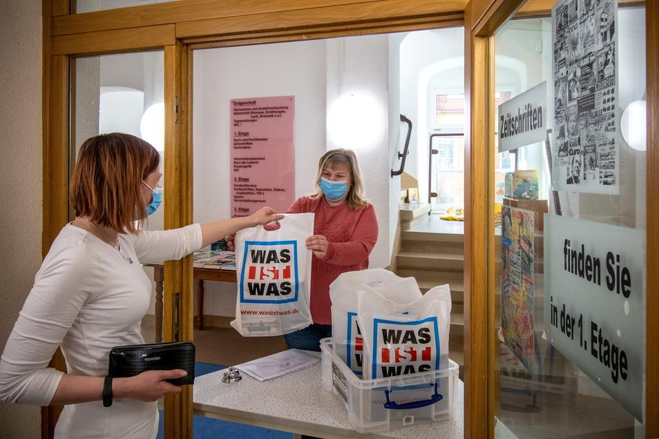 Swetlana Schmalz übergibt in der Döbelner Stadtbibliothek ein bestelltes Bücherpakete.