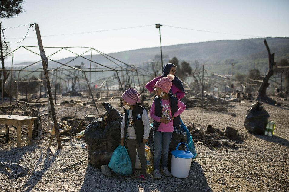 Eine Familie steht innerhalb des ausgebrannten Flüchtlingslagers Moria. Zuletzt hielten sich in Moria und unmittelbarer Umgebung etwa 12.500 Migranten auf.