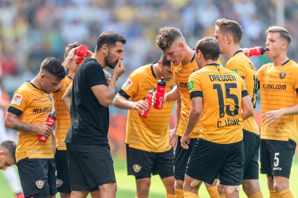 Dynamos Trainer Cristian Fiel nachdenklich mit seinen Spielern in einer Trinkpause.
