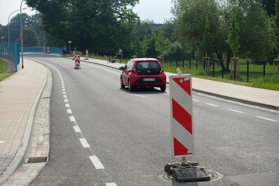 Baken stehen auf der Auffahrt zur Brücke Schillerstraße. Die Gullydeckel mussten gehoben werden.