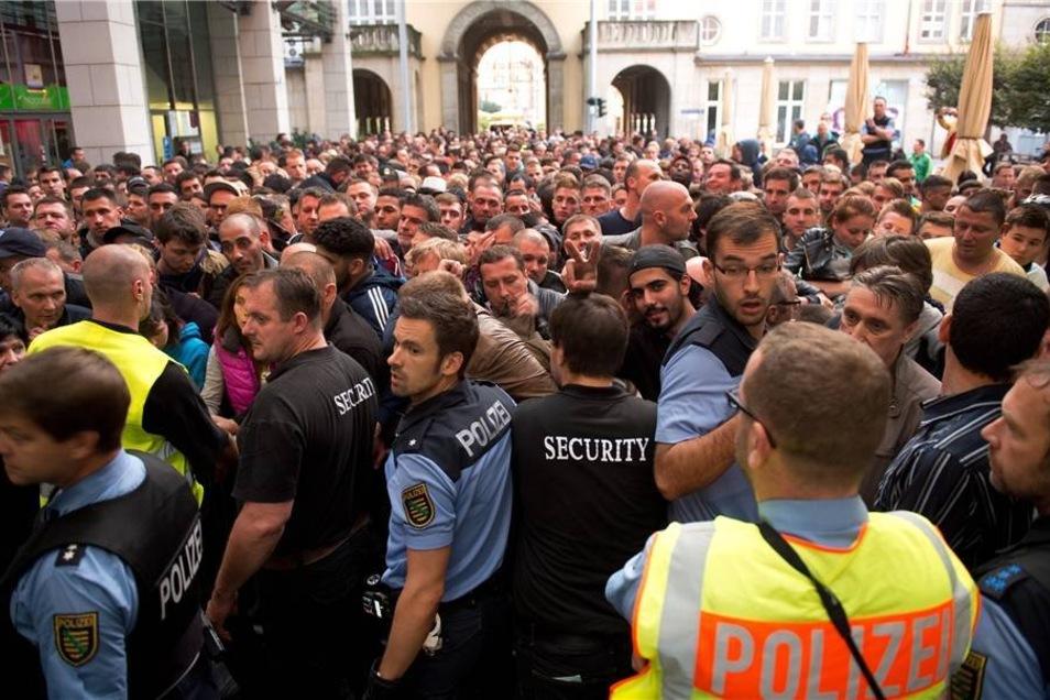 Die Dresdner Innenstadt am Freitagmorgen: Polizisten müssen den Eingang zur Altmarktgalerie sichern, in desse Nähe sich ein Apple-Store befindet.