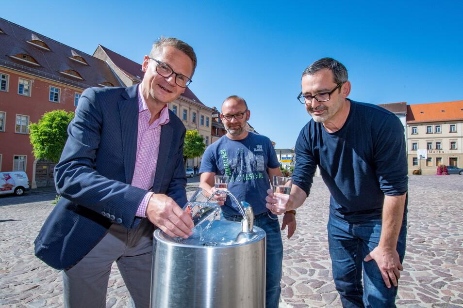 Bürgermeister Veit Lindner (von links), Jens Döge von der Firma LFT und Matthias Lange vom Bauamt weihen den Trinkbrunnen ein.