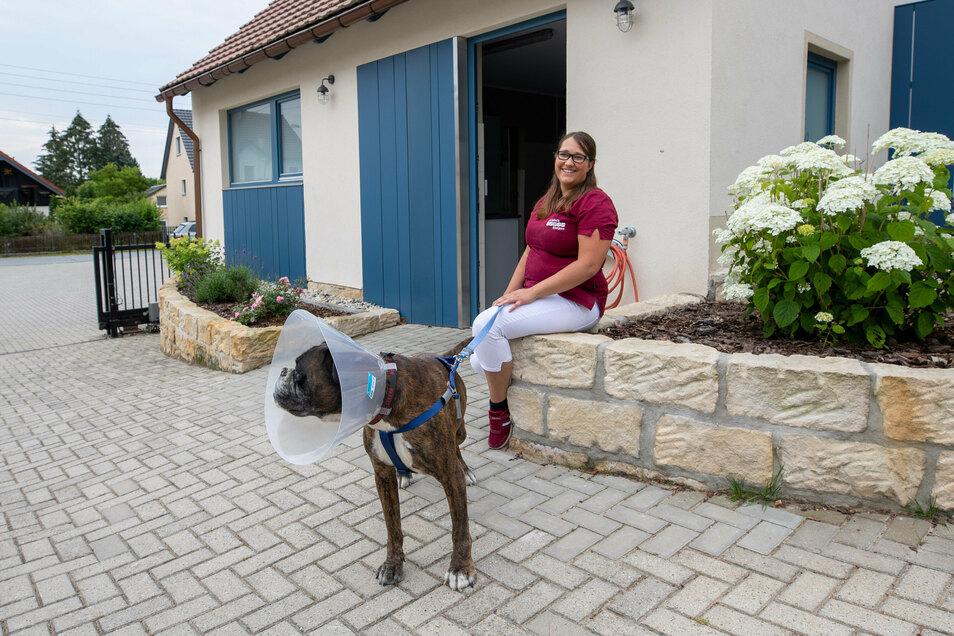 Rosalie Kaiser sitzt mit einem Hund, der eine Behandlung bekommen hat und jetzt einen Leck-Schutz trägt, vor der neuen Intensivstation.