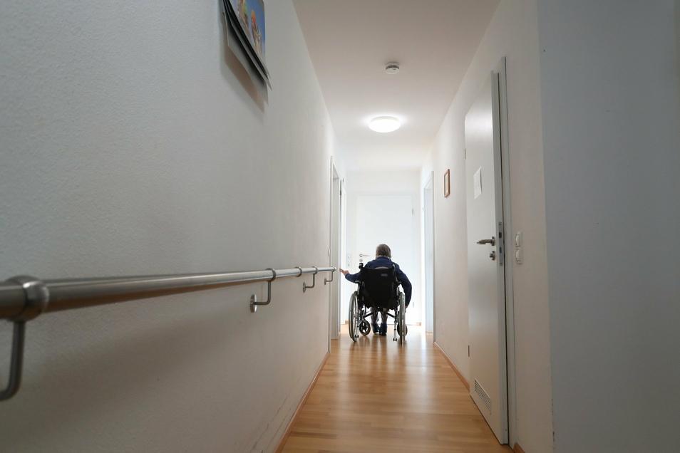 Eine Rollstuhlfahrerin fährt in einer Wohngemeinschaft einen Flur entlang zu ihrem Zimmer. Isolation und das Umschalten auf Digitales macht die Corona-Krise für viele Behinderte besonders belastend.