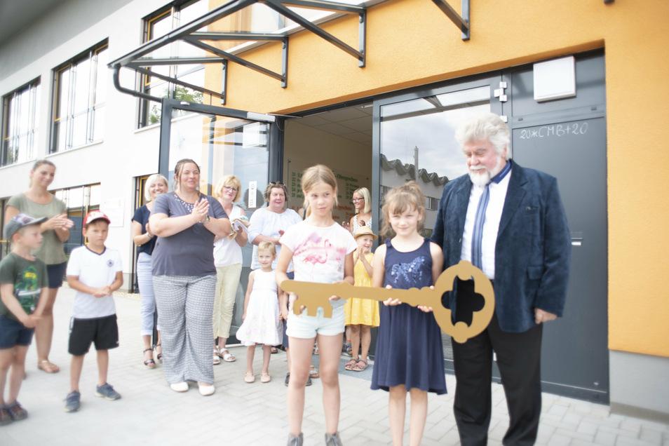 Mit einem großen Schlüssel nahmen Kinder des neuen Hortes Räckelwitz das neue Gebäude in Besitz. Bürgermeister Franz Brußk (r.) freut sich mit ihnen.