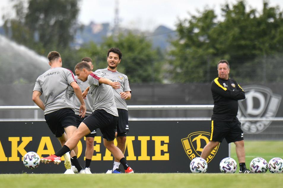 Dynamo ist wieder am Ball wie hier Chris Löwe (vorn) beim Trainingsauftakt. Trainer Markus Kauczinski (r.) beobachtet die ersten Kurzpassfolgen.