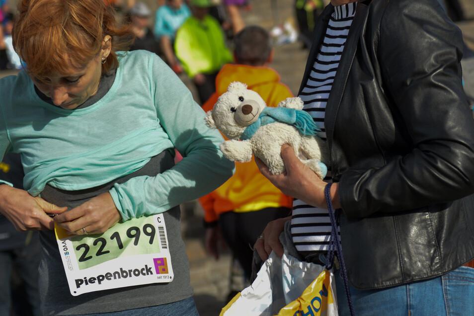Glenn, Emily aus den USA befestigt vor dem Start ihre Nummer. Sie läuft den Halbmarathon. Foto: Cristian Juppe
