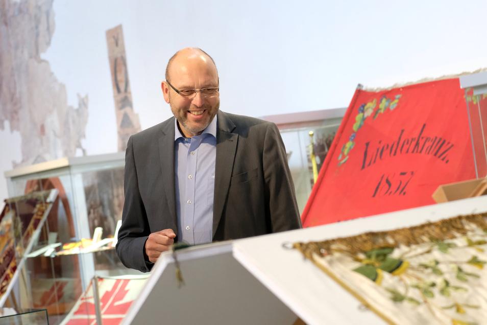 Gehörte zu den ersten Besuchern: Meißens Oberbürgermeister Olaf Raschke (parteilos) bewundert die kunstvoll gestickten Vereinsfahnen in der neuen Sonderschau des Museums.