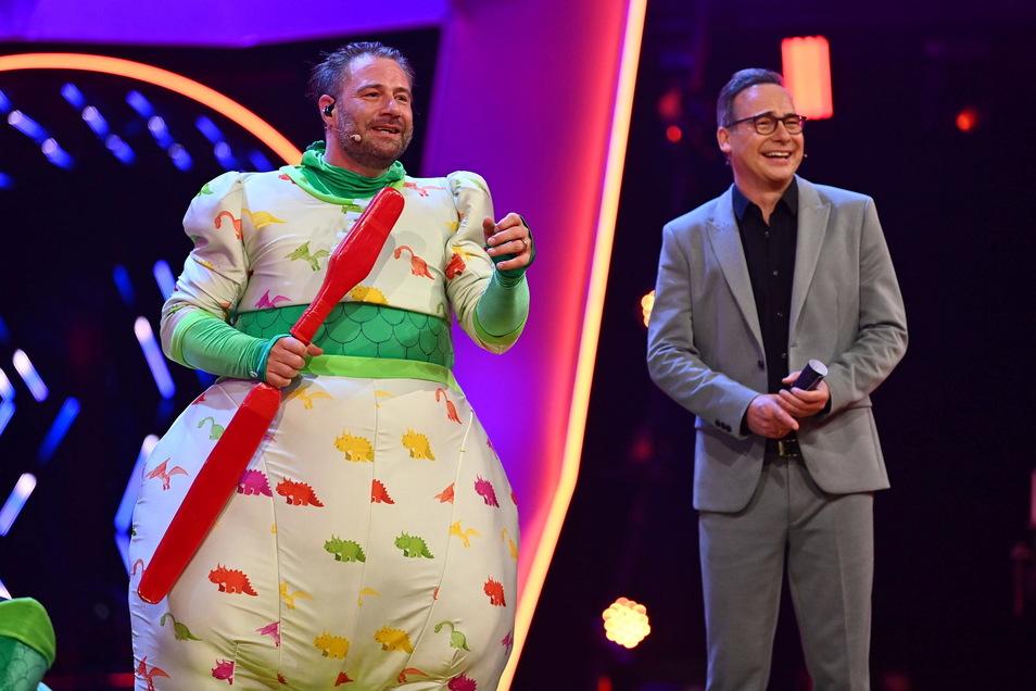 Der Sänger Sasha (l) jubelt im Finale der ProSieben-Show «The Masked Singer» im Kostüm des Dinos neben Moderator Matthias Opdenhövel über seinen Sieg.