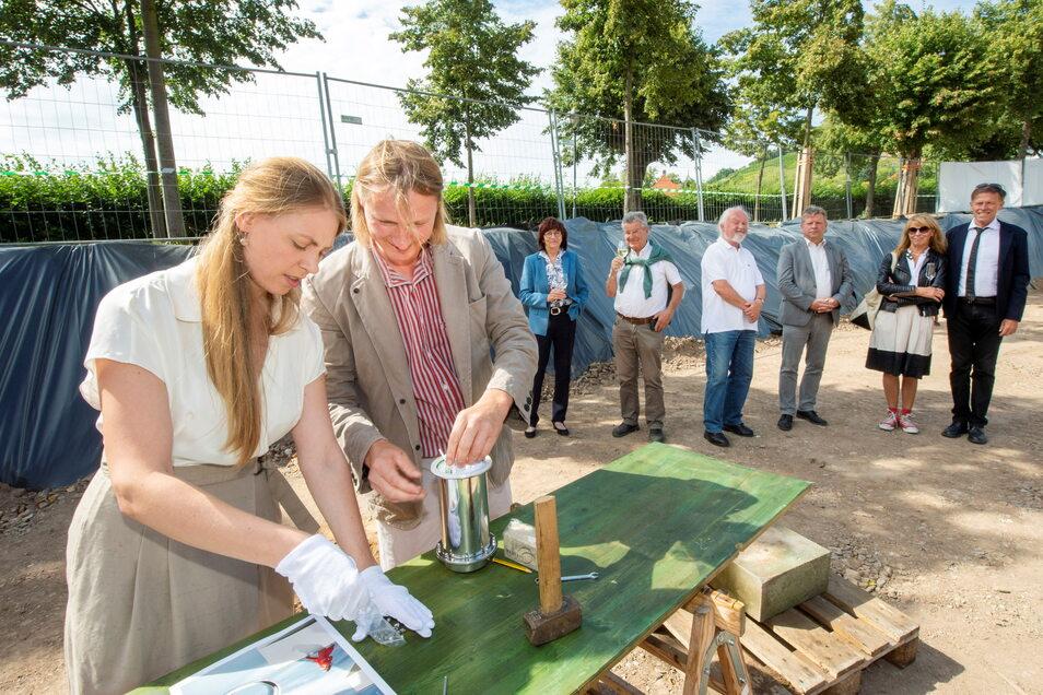 In der Baugrube für den neuen Weinkeller befüllt Karl Friedrich Aust mit seiner Lebenspartnerin Carolin Netsch die Kapsel mit Zeitdokumenten.