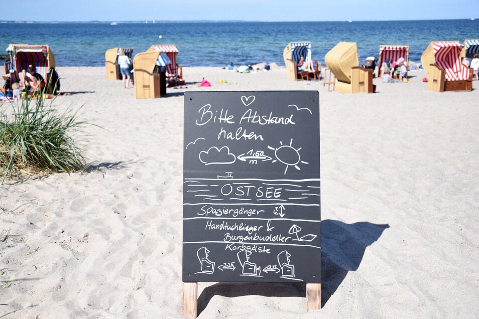 """Schleswig-Holstein, Niendorf: Ein Schild mit der Aufschrift """"Bitte Abstand halten"""" steht am Zugang zum Strand an der Ostsee."""