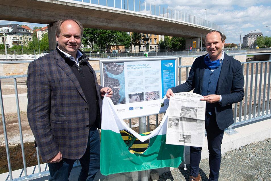 Oberbürgermeister Dirk Hilbert (l.) und Umweltminister Wolfram Günther enthüllen bei der Übergabe am Weißeritzknick eine Tafel für den künftigen Hochwasser-Lehrpfad. Der Minister zeigt eine SZ vom August 2002. Genau hier schossen die Wassermassen damals i