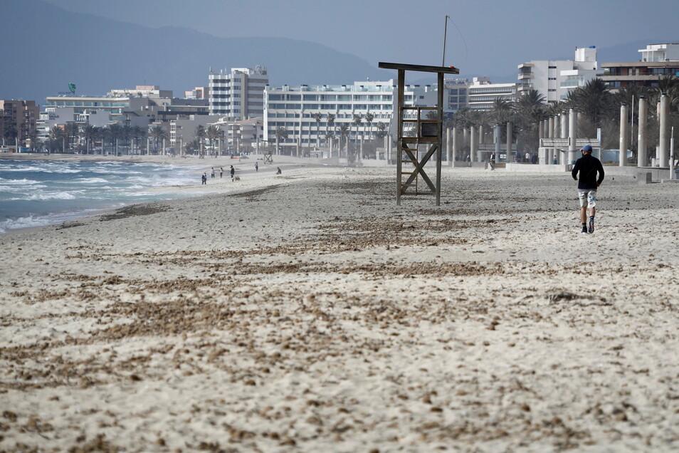 Ein Mann geht in Palma am Strand von Arenal über den Sand. Mallorca gilt ab Sonntag nicht mehr als Corona-Risikogebiet.