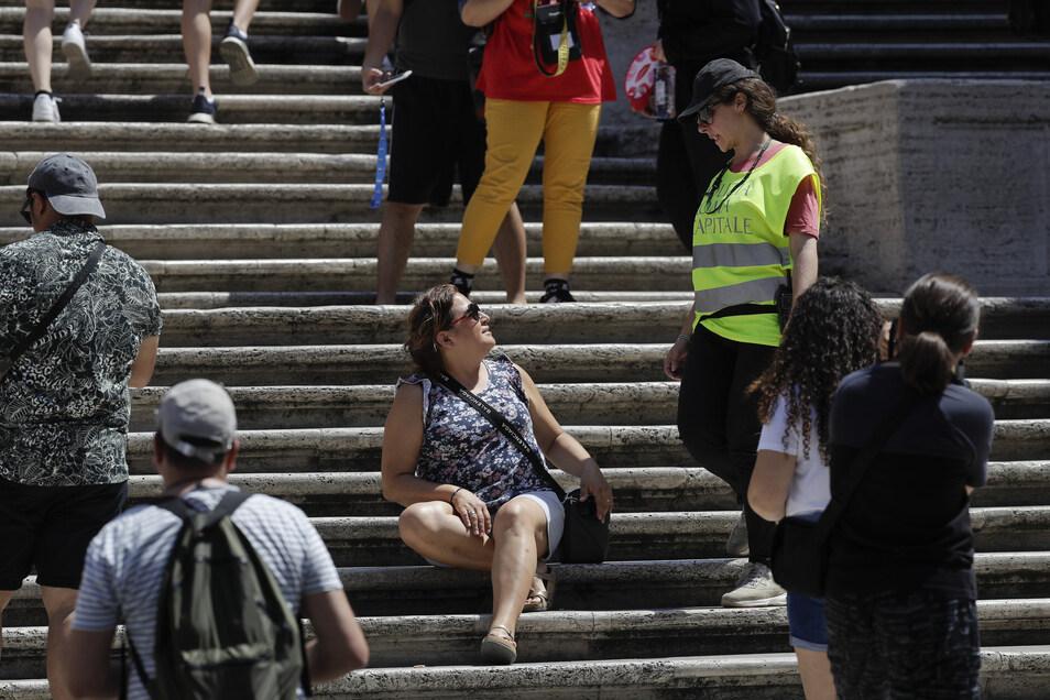 Eine Polizistin fordert eine Frau auf der Spanischen Treppe auf, nicht auf der Treppe zu sitzen.
