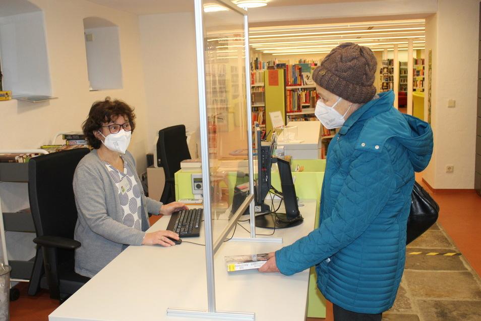 Marita Knispel (rechts) leiht sich Bücher in der Stadtbibliothek Gröditz aus. Inka Wirtjes (links) freut sich, dass Stammleser trotz Corona die Treue halten.