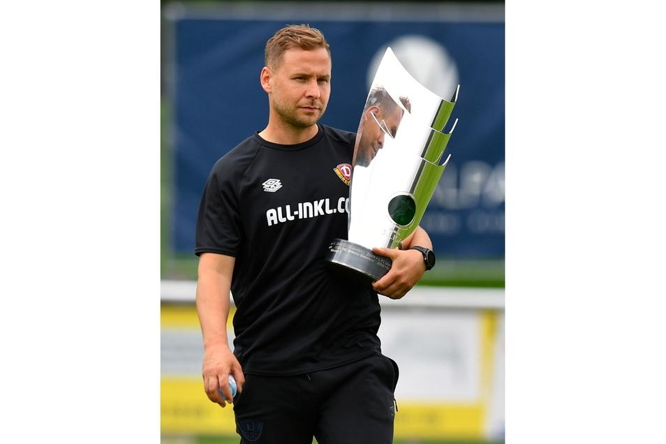 Henry Buschmann hält den Pokal für den Drittliga-Meister 2021 im Arm. Als Pressesprecher und Fan hat er Dynamo auf eine sehr emotionale Weise begleitet.