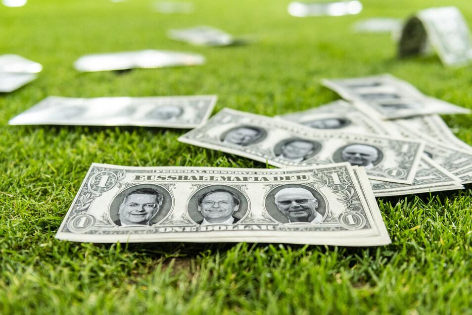 Dollarscheine auf dem Rasen im Dresdner Rudolf-Harbig-Stadion, darauf die Porträts vom damaligen DFB-Präsidenten Reinhard Grindel, sowie Rainer Koch und Franz Beckenbauer. Eine Protestaktion der Dynamo-Fans.
