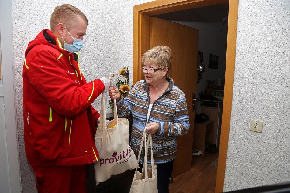 Einkaufsübergabe an der Haustür: Gabriele Weida (r.) bekommt ihre Einkäufe überreicht. So muss die Krebspatientin nicht selbst in den Supermarkt.