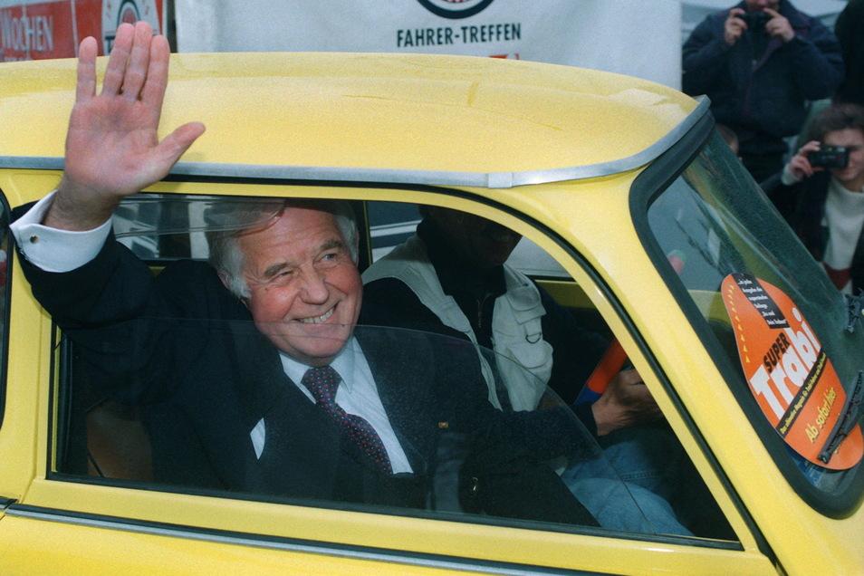 Kurt Biedenkopf (CDU) winkt in Dresden als neuer Besitzer eines gelben Trabant 601 vom Beifahrersitz den Fotografen zu. Das Auto mit dem Kennzeichen BI-KO 601 ist eine Geschenk der Organisatoren des Trabantfahrertreffens in Zwickau.