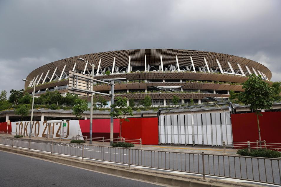 Dunkle Wolken hängen am Himmel über dem neuen Nationalstadion in Tokio, an dem wenige Wochen vor der Eröffnung der Olympischen und Paralympischen Spiele die Bauarbeiten noch im Gange sind.