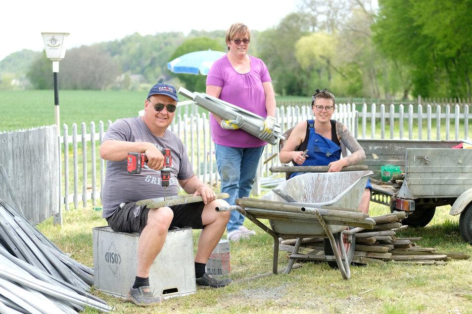 Jens Böhm, Ute Böhm und Dana Winter (v.l.) erneuern den Zaun rund um den Biergarten.