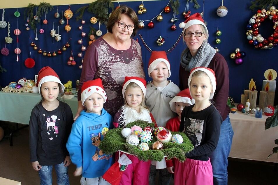 """Die Kinder aus der Kita """"Wirbelwind"""" staunten nicht schlecht, was es alles für Weihnachtskugeln gibt. Sie kamen mit Erzieherin Melanie Richter (r.), daneben Karin Turek vom Heimatverein, der die Ausstellung initiiert hat."""