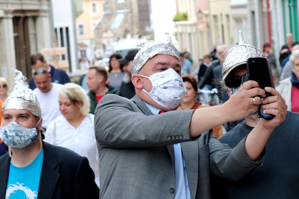 Meißner Vertreter der Satire-Truppe Die Partei haben sich Montagabend unter rund 200 Protestler gegen die Auflagen im Zuge der Corona-Krise gemischt. Sie spielen auf Verschwörungstheorien an.