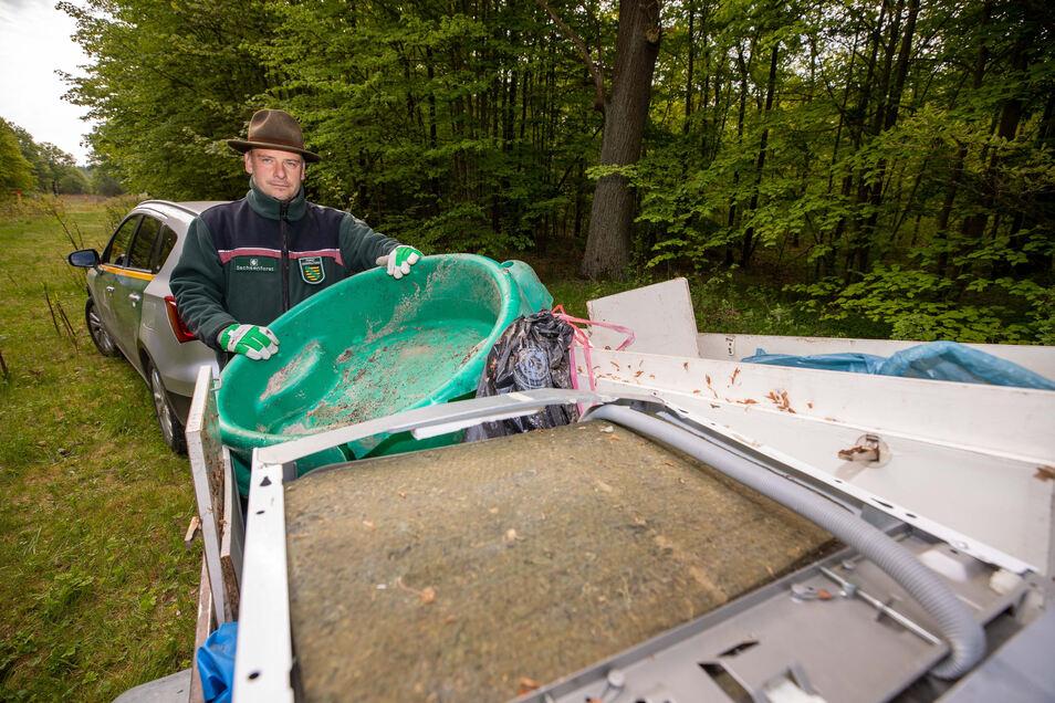 Revierförster Michael Blaß hat in seinem Anhänger gesammelten Sperrmüll im Wald bei Graupa verstaut. Ganz oben liegt eine Geschirrspülmaschine, die illegal entsorgt wurde.