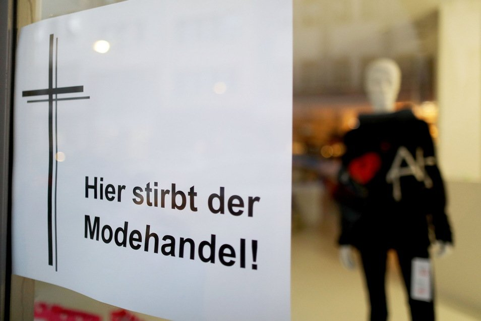 """Ein Plakat mit der Aufschrift """"Hier stirbt der Modehandel"""" hängt im Schaufenster eines Kölner Geschäftes."""