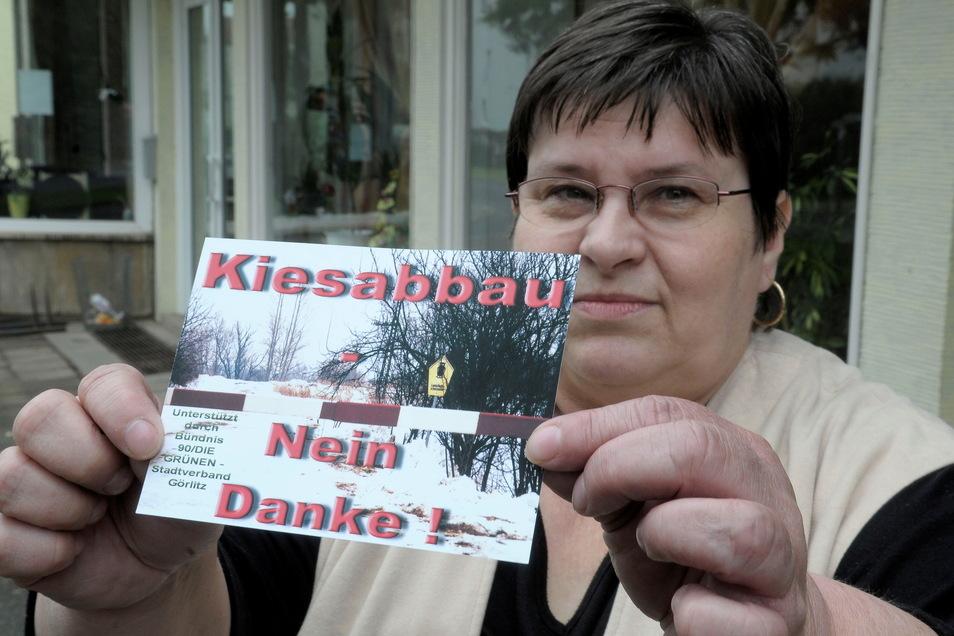 Elisabeth Barthel vom Interessenverein Wohnpark Hagenwerder zeigt eine Postkarte, mit der schon 2009/10 gegen den Kiesabbau in Hagenwerder an der B 99 protestiert wurde.