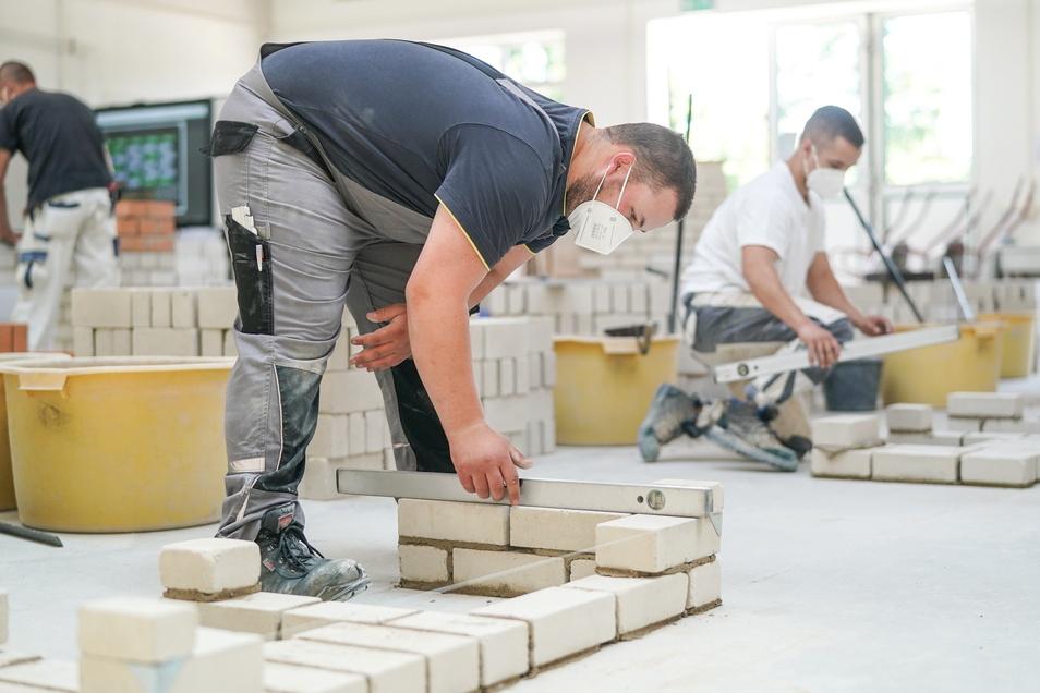 Bau-Azubis in der Werkstatt des Überbetrieblichen Ausbildungszentrums Bau Bildung e.V. an einer Übungsmauer.